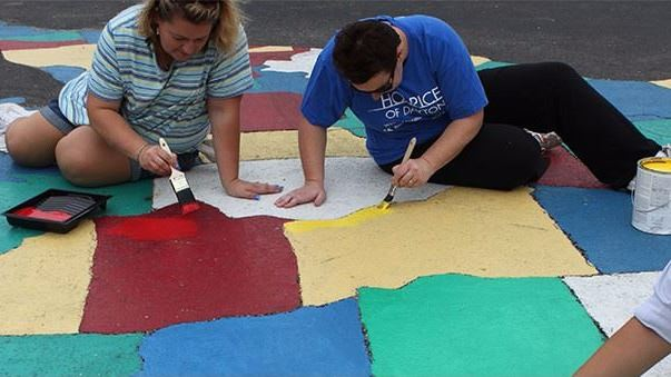 Small group painting the United States on the pavement